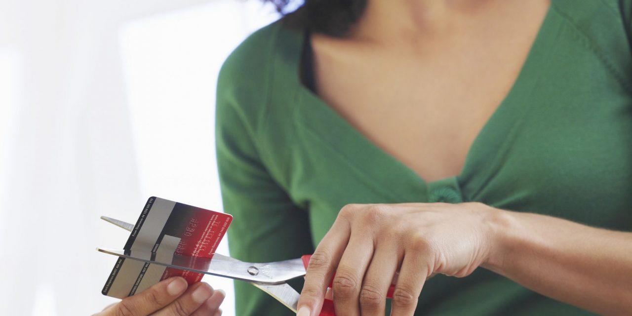 Pessoa cortando cartão com tesoura - Paraná Banco